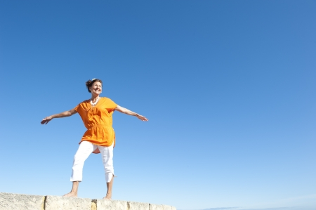 Active and attractive senior woman happy balancing on top of wall, smiling and relaxed, isolated with blue sky as background and copy space. Stock Photo