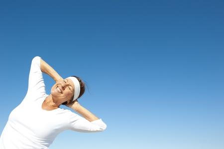 Attivo e attraente donna senior in posa felice e gioiosa in una giornata di sole, isolato con cielo blu come sfondo e copia spazio. Archivio Fotografico