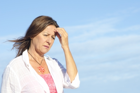 worried woman: Worried and concerned looking senior woman outdoor, isolated with blue sky as background and copy space.