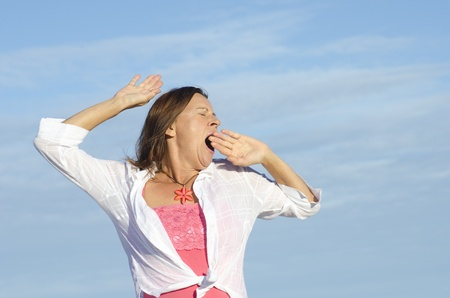 yawning: Attractive senior woman stretching and yawning, isolated with blue sky as background and copy space. Stock Photo
