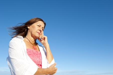 Outdoor portrait of attractive mature woman looking thoughtful, worried, isolated with blue sky as background and copy space. Stock Photo - 15376614