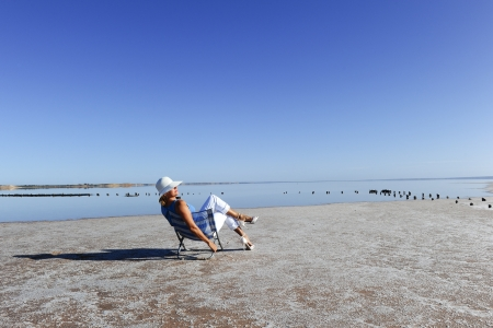 Sexy mature woman sitting relaxed at salt lake in remote outback Australia, wearing high heels and and white rimmed summer hat, isolated with water and sky as background and copy space. Stock Photo - 15376895