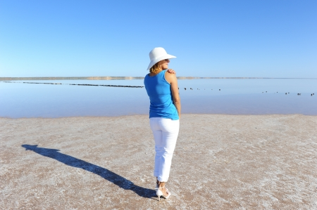 Sexy mature woman standing relaxed at salt lake in remote outback Australia, wearing high heels and and white rimmed summer hat, isolated with water and sky as background and copy space. photo