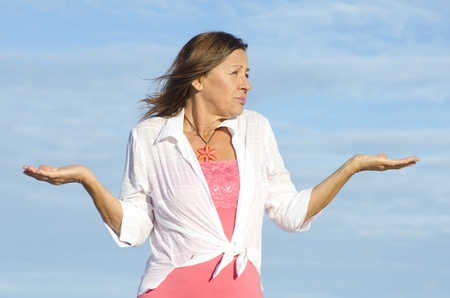 unknowing: Mature woman shrugging innocent and confused shoulders, gesturing with arms up, isolated with blue sky as background and copy space.