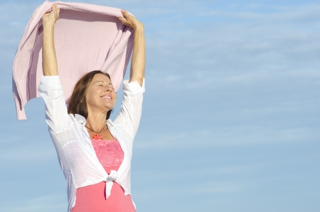mature woman sexy: Cheerful, happy smiling attractive senior woman enjoying retirement, isolated, with blue sky as background and copy space.