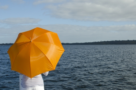 finds: Anonymous woman finds shelter under bright orange umbrella standing at dark water of lake, with coastline and cloudy sky as background and copy space.