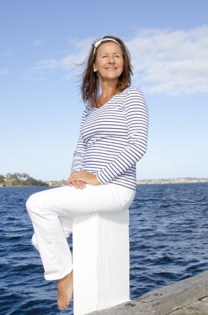 Portrait happy relaxed attractive looking senior woman sitting on pier overlooking marina, isolated with water, coastline and sky as background and copy space. photo