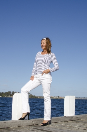 Sexy looking senior woman enjoying relaxed active retirement at seaside, isolated with water, shoreline and blue sky as background and copy space. Stock Photo - 15377027