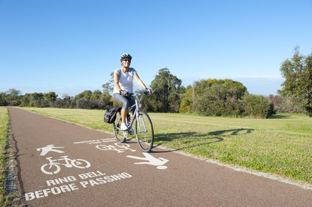 healthy path: Happy mature woman cycling along path in park, with warning symbol on ground, with blue sky and park as background and copy space. Stock Photo