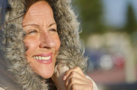 Portrait of attractive looking senior woman keeping herself warm in cold winter weather, isolated with furred hood covering head and blurred background as copy space. photo