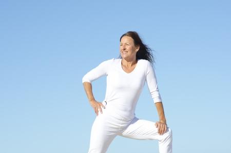 mujer sola: Positiva y activa mujer jubilada feliz maduro en blanco ejercicios de estiramiento, aisladas con el cielo azul como fondo y espacio de la copia. Foto de archivo
