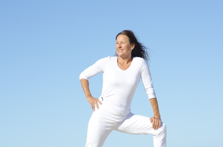 senior woman exercising: Positive and happy active retired mature woman in white stretching exercises,  isolated with blue sky as background and copy space.