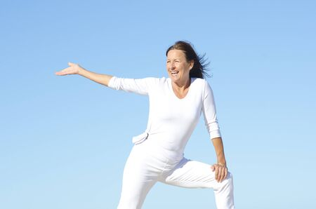 Cheerful attractive senior woman being happy and active, isolated with blue sky as background and copy space photo