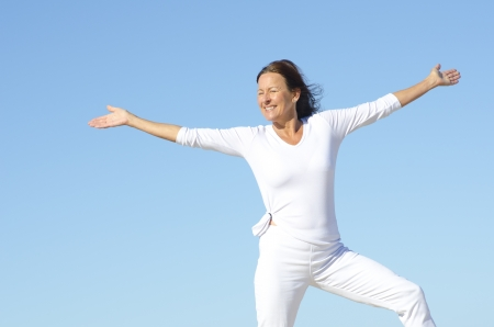 Sporty attractive senior woman being happy and active, isolated with blue sky as background and copy space photo
