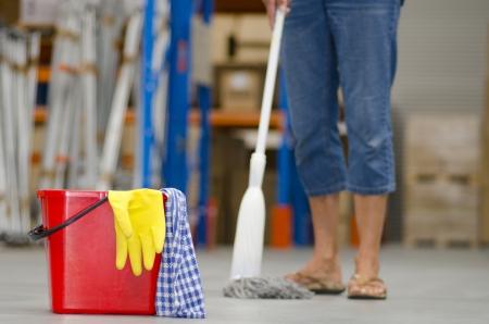Business Reinigung von Industrie-Lager mit isolierten roten Eimer, gelben Handschuh und Beine der weiblichen Reiniger in unscharfen Hintergrund und Kopie Raum.