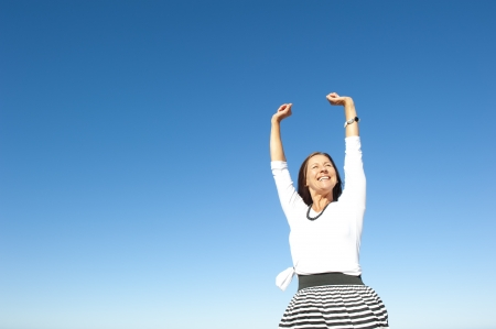 Attractive and successful looking mature woman cheerful and happy with arms up, isolated with blue sky as background and copy space. Stock Photo - 15376608