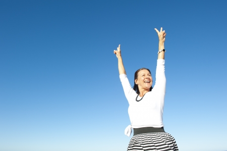 Attractive and successful looking mature woman cheerful and happy with arms up, isolated with blue sky as background and copy space. Stock Photo - 15376567