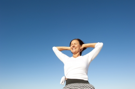 Attractive and successful looking mature woman cheerful and happy with arms up, isolated with blue sky as background and copy space  Stock Photo - 15377987