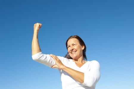 senior exercising: Confident focused and physical strong mature woman showing off her biceps, isolated with blue sky as background and copy space