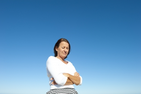 Portrait worried, thoughtful, depressed mature woman outdoor, isolated with blue sky as background and copy space  Stock Photo - 15377947