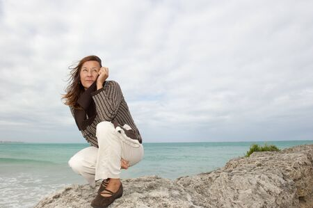 Pretty senior woman with natural confident look at cold windy stormy weather at ocean, isolated with sea and dark cloudscape as background and copy space. photo