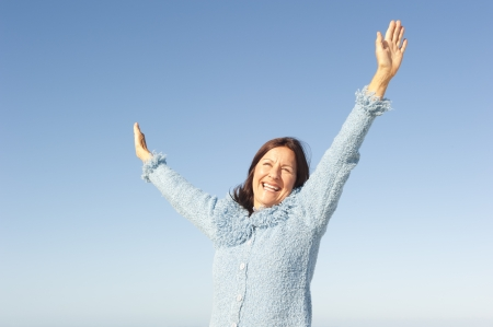 positive feelings: Positive, optimistic and happy active retired senior woman posing with arms up and smile, isolated with blue sky as background and copy space. Stock Photo