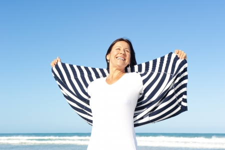 feelings of happiness: Pretty happy and relaxed senior woman feeling good and joyful, isolated with  ocean and blue sky as background and copy space.