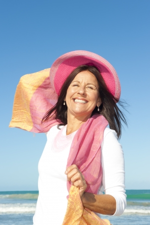 scarf beach: Beautiful senior woman smiling happy at beach holiday, isolated with blue sky and ocean as background and copy space. Stock Photo