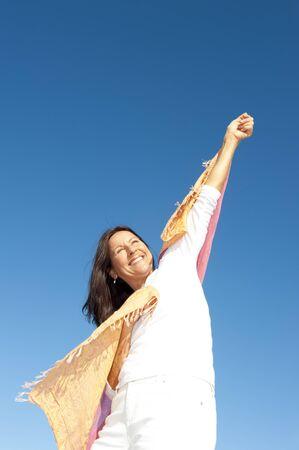 actitud positiva: Sexy mujer mayor jubilada fiesta alegre, aislada con el cielo azul como fondo y espacio de la copia.
