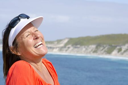 Portrait of happy attractive looking mature middle aged woman joyful laughing, isolated with sunshine on face, ocean, sly and coastline as background and copy space. Stock Photo - 15378115