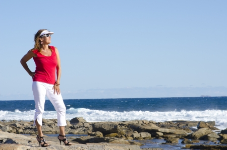 Sexy middle aged woman standing at the ocean wearing red top, white pants and high heel shoes, isolated with happy relaxed smile and sea and blue sky as background and copy space. photo