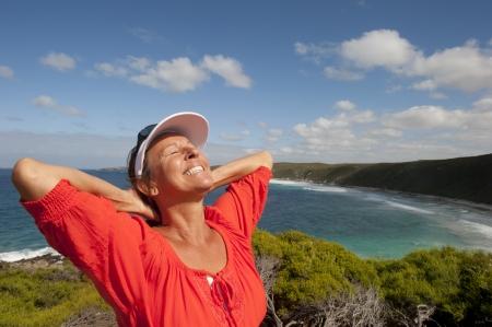 Ritratto di felice attraente cercando maturo gioioso met� donna di et� compresa tra ridere, isolato con il sole sul viso, oceano, sornione e costa come sfondo e copia spazio.