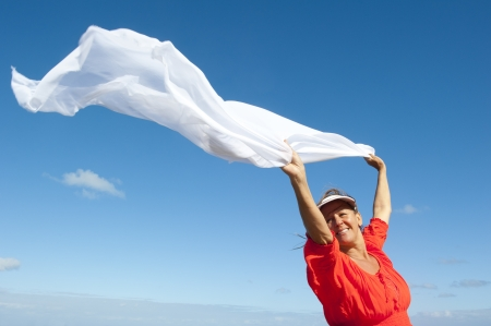 Cheerful, joyful, happy mature woman holding white fluttering cloth in the wind, isolated with blue sky as background and copy space. photo