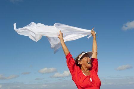 Vrolijke, vrolijke, gelukkige volwassen vrouw met witte fladderende doek in de wind, geïsoleerd met blauwe hemel als achtergrond en kopieer de ruimte.