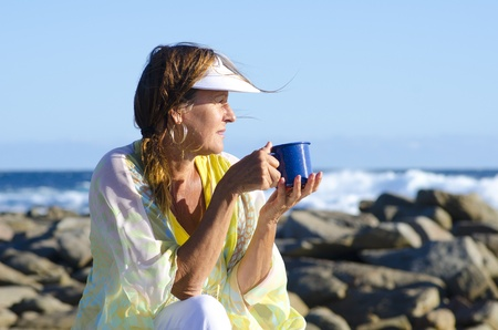 An attractive looking mature woman sitting relaxed at the ocean with cup of tea or coffee, isolated with sea and blue sky as background and copy space. photo