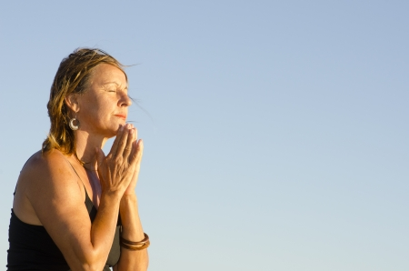 Attractive looking middle aged woman sitting relaxed with closed eyes meditating, praying at sunset, isolated with blue sky as background and copy space. photo