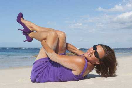 Pretty looking mature woman in sexy purple dress and high heel shoes at the beach, with ocean and blue sky as background and copy space. photo