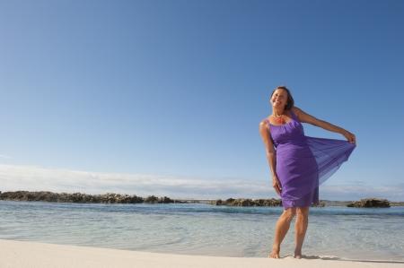 donne mature sexy: Piuttosto cerca donna matura in sexy abito viola alla spiaggia tropicale, con mare e cielo azzurro come sfondo e copia spazio. Archivio Fotografico