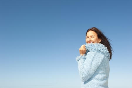 Portrait of confident and happy relaxed looking attractive senior woman enjoying active retirement in winter sun, isolated with blue sky as background and copy space  photo