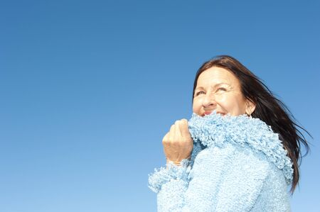 Portrait of confident and happy relaxed looking attractive senior woman enjoying active retirement in winter sun photo