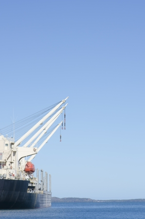 anchoring: Freight vessel ship with cranes anchoring, with ocean, coastline and blue sky as background and copy space.