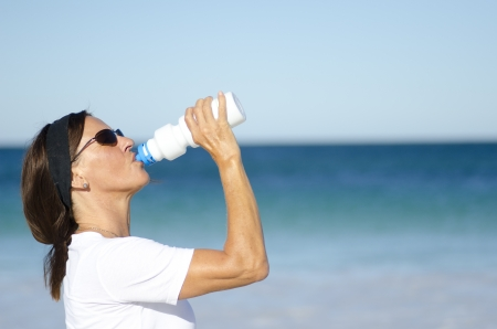dehydrated: Attractive and active senior woman drinking refreshing water after exercising, isolated with ocean and blue sky as background and copy space.