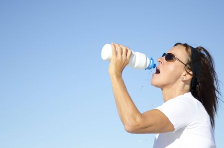 dehydrated: Attractive and active mature woman drinking refreshing water after exercising, isolated with blue sky as background and copy space. Stock Photo