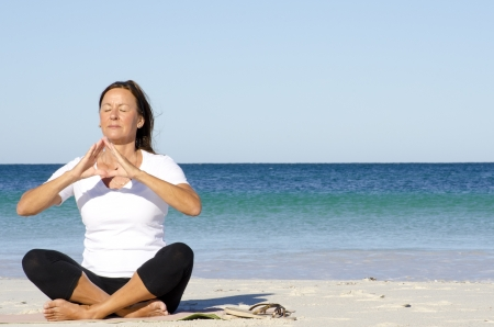 keeping fit: Attractive and active senior woman keeping fit with yoga and meditation at beach, isolated with ocean and blue sky as background and copy space. Stock Photo