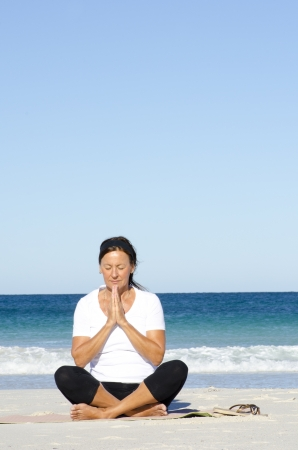 Attractive and active senior woman keeping fit with yoga and meditation at beach, isolated with ocean and blue sky as background and copy space. photo