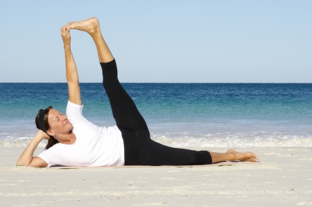 enjoy space: Attractive and active senior woman keeping fit and healthy with stretching pilates exercises at beach, with ocean and blue sky as background and copy space. Stock Photo