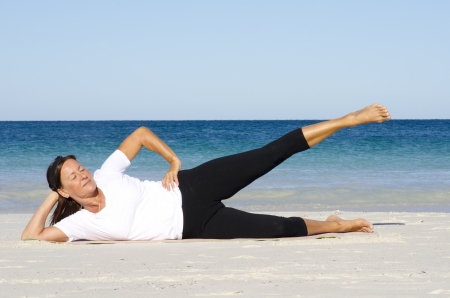 Attractive and active senior woman keeping fit and healthy with stretching pilates exercises at beach, with ocean and blue sky as background and copy space. photo