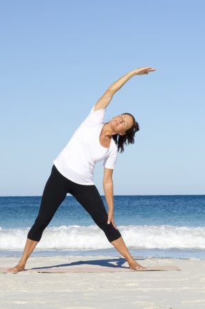 keeping fit: Attractive and active senior woman keeping fit and healthy with stretching pilates exercises at beach, with ocean and blue sky as background and copy space. Stock Photo