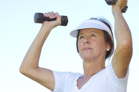 determined: Portrait attractive fit and active senior woman exercising with weights, isolated with blurred outdoor background.