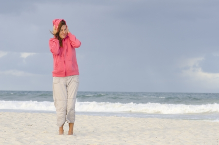rain coat: Lonely mature woman at beach wearing warm hooded jumper, isolated with wild ocean and dark storm sky as background and copy space. Stock Photo